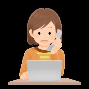 パソコンの前で電話をする一般人女性